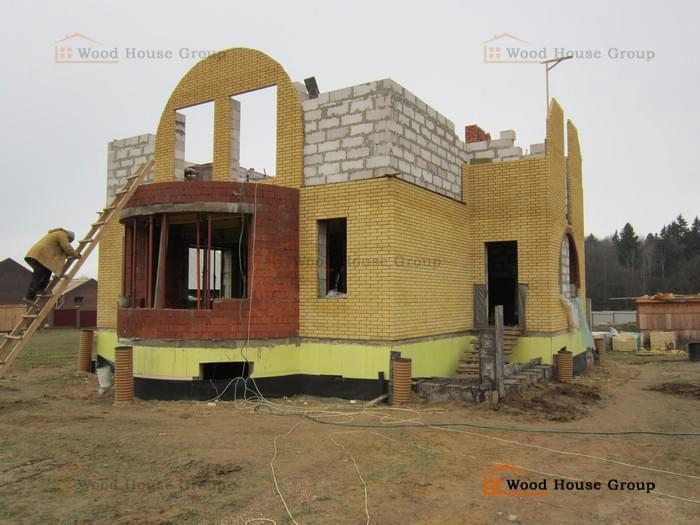Дом с цокольным этажом из газоблоков, с кирпичной облицовкой фасада